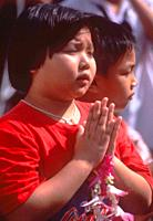 "girl, Buddhist, """"praying"""", with flower offering, Thailand."
