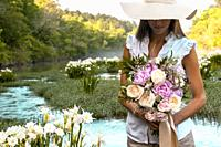 A partial view of a young woman holding a bouquet of flowers standing in a shallow river with wild Cahaba lillies in the background.