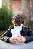 young boy with mask reads on tablet, remote school, sad look sitting in the garden.