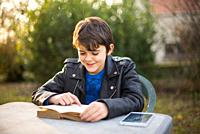 young boy reads book, smiling, sitting in garden, tablet on table.