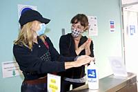 Two friends with masks sanitizing hands with hydrogel