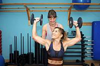 Two young women exercising in gym, doing weight workout