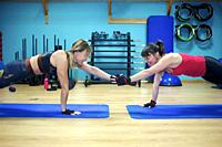 Two women look at each other and laugh awith extended arms a at the gym. They are also using exercise mats.