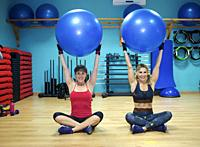 Two young women exercising in gym, using inflatable exercise ba