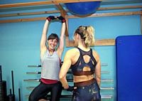 A mid adult woman in his 30s working as a fitness instructor in a gym, helping a freind in her 30s strengthening her arms. They are both Europeans