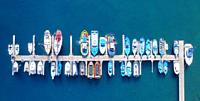 Panoramic Aerial view on boats moored in the pier, drone shot directly above. High quality photo.