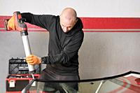 Glazier applying rubber sealing to windshield in garage, close up. High quality photo.