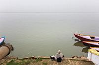 An unidentified person rests on the banks of the Ganges River in Varanasi, India.