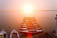 Sunrise over the Ganges river, with tour boats in the foreground in Varanasi, India.