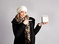 Pretty young woman poses with winter clothes and showing a gift with cheerful and friendly fitness.