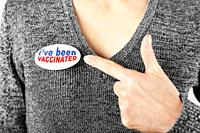 Middle age caucasian female in grey sweater pointing with her finger at button pin with text I've been vaccinated.