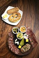german cold cuts tapas snack platter with meats and bread on wood table background.