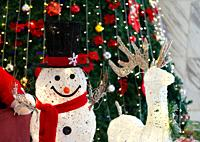 Smiling face snowman decoration and deer near christmas tree. Winter holiday style.