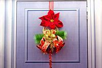 Beautiful christmas ornament flower, jingle bell hang at door.