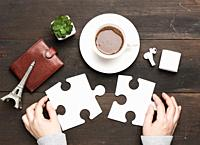 white cup with cocoa and two female hands holding white puzzle pieces on a brown wooden background, top view.