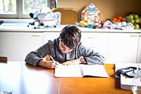 kid boy does homework on the table at home in the kitchen.