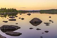 Landscape in evening light with mountains in background, clear sky and rocks in the water, Swedish Lapland, Sweden.