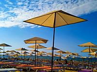 A lot of Beach Umbrellas along the Coastal Area in Summer.