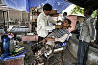 Bundi India - August 2020: A barber working under a tree on the street in the old town of Bundi on August 9, 2020 in Bundi, Rajasthan. India.