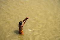 Varanasi, India - September 2020: A men making an offering on the Ganges River in Varanasi on September 11, 2020 in Uttar Pradesh, India.