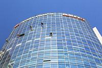 Window washers hanging from ropes on outside of modern curved architectural glass and steel office tower, Tel Aviv, Israel.