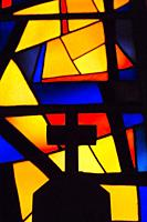 Silhouetted cross and colourful stained glass window inside The Church of the Annunciation, Nazareth, Israel.