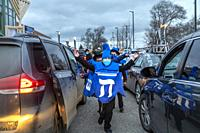 Southfield, Michigan - Boys dance between cars lined up for a Car Top Menorah Parade on the fourth night of Chanukah.