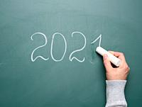 female hand holds a piece of white chalk and writes on a green school board 2021, new year.