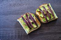 Toast with avocado and anchovy spread.