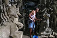Kolkata, India - September 2020: A craftsman making clay and straw sculptures for the Durga Puja festival in Kumartuli, the potters' district of north...