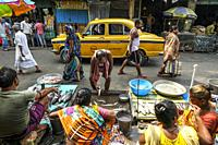 Kolkata, India - October 2020: A taxi passing in front of some stalls selling fish in the New Market on October 8, 2020 in Kolkata, West Bengala, Indi...