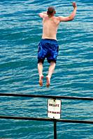 Male jumping off of a railing into water with sign saying Unsafe for swimming.