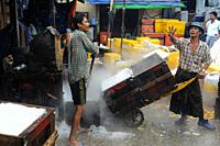 Yangon, Myanmar, Asia - A worker transports wooden crates filled with crushed ice on a handcart at the traditional Baho San Pya Fish Market, a wholesa...