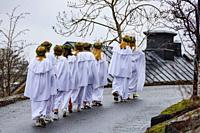 Stockholm, Sweden A school group in Liljeholmen march in a traditional Santa Lucia celebration with song.