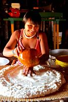 Young native indian woman preparing forming maniok flour to a dough in a traditional way, Mato Grosso, Brazil, South Amreica.