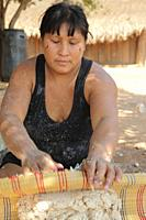 Young native indian woman washing maniok flour in a traditional way, Mato Grosso, Brazil, South Amreica.