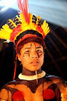 Portrait of young indio tribes man in festive costume and feathers in his hair, Mato Grosso, Brazil, South America.