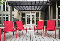 Patio doors and brown pergola structure over wooden deck with red canvas armchairs at rear of contemporary khaki painted vertical wood plank cladded h...