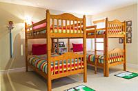 Bunk beds with colourful bedspreads and folk art in kid's carpeted bedroom on upstairs floor inside contemporary home, Quebec, Canada. This image is p...