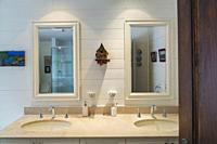 White wooden cabinet with nuanced tan marble countertop and oval shape sunken sinks, large wall mirrors and folk art objects in guest bathroom on upst...