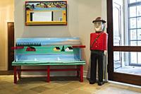 Canadian Mountie and blue, green and red painted folk art sitting bench next to entryway inside contemporary home, Quebec, Canada. This image is prope...