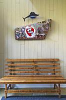 Wood plank sitting bench and Volkswagen hood panel decorated with Canadian and U. S. pennies and dollar store objects by folk art artist David Stephen...
