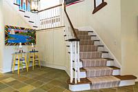 Oak wood staircase with white painted balustrades and tan nuanced striped rug runner leading to upstairs floor inside contemporary home, Quebec, Canad...