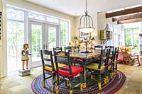 Colourful acrylic painted pine wood dining table with high back chairs on weaved checkered oval rug in dining room with earth-toned nuanced ceramic ti...