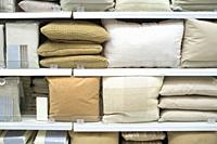 Bright pillows and bed wear on shelves. Selective focus.