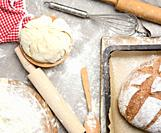 bread, kneaded dough of white wheat flour lies on a wooden plate and a wooden rolling pin, top view.