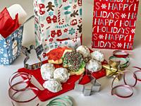 Assorted Christmas cookies on a red cutting board with holiday packages and ribbon.