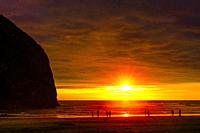 Colorful Sunset Tourists Haystack Rock Sea Stack Canon Beach Clatsap County Oregon. Orginally discovered by Clark of Lewis Clark in 1805.