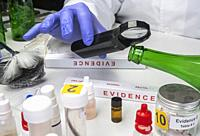 Police expert gets blood sample from glass bottle in Criminalistic Lab.