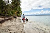 young male tourist walking barefoot on sandy beach, Colon Island, Bocas del Toro Archipelago, Bocas del Toro Province, Panama, Central America, Americ...